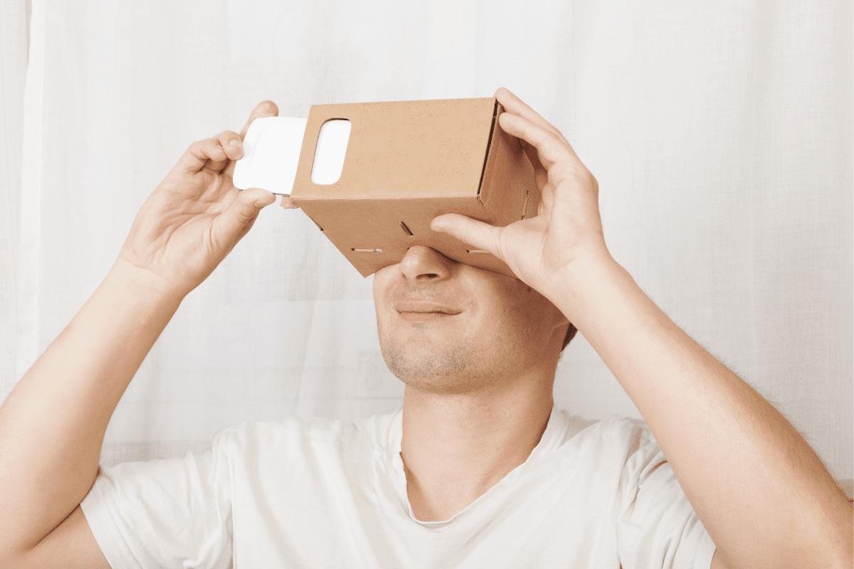 Adult man using cardboard virtual reality gloves cardboard